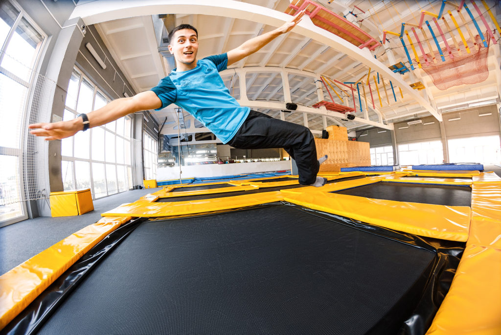 Happy emotional man jumping and flying in trampoline sport center indoors